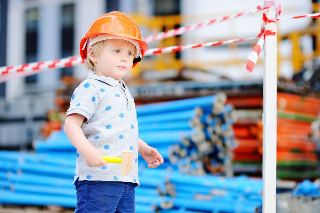 Small child in hardhats with hammer working outdoors
