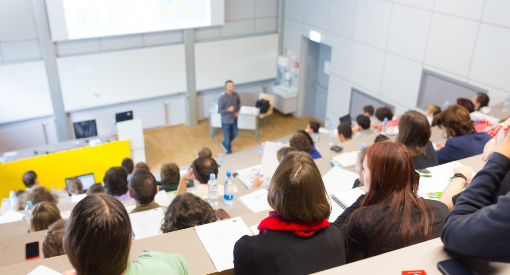 Speaker giving presentation in lecture hall at university. Students listening to lecture and making notes.