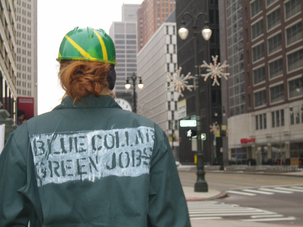 "Worker wearing a shirt that reads ""blue collar, green jobs"""
