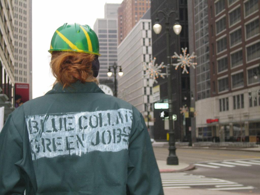 """Worker wearing a shirt that reads """"blue collar, green jobs"""""""