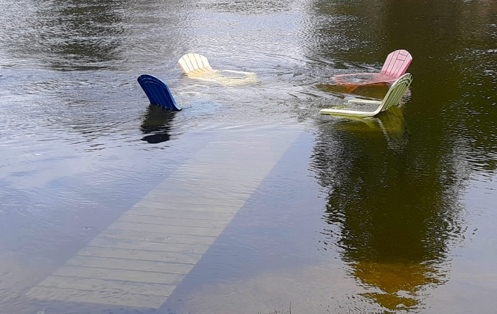 Flood waters rise above lawn chairs