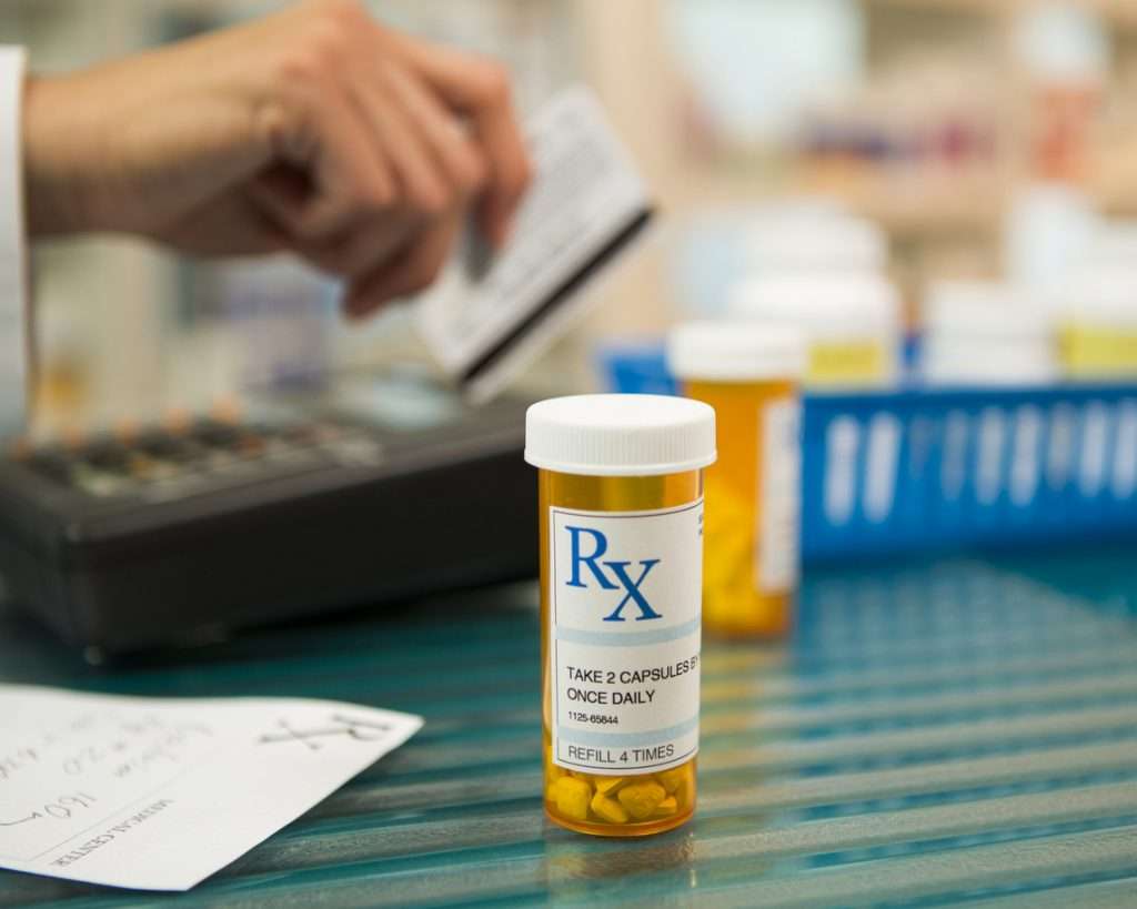 Closeup of prescription bottle with pharmacist using credit card.
