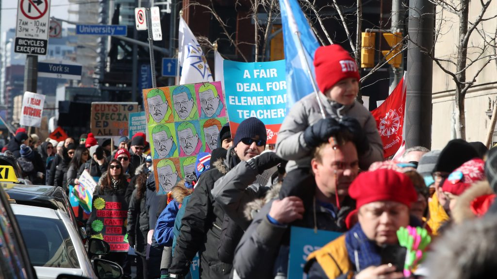 Teachers march, chant and sing crowding the sidewalk outside the Royal York as Education Minister Stephen Lecce speaks to the Canadian Club