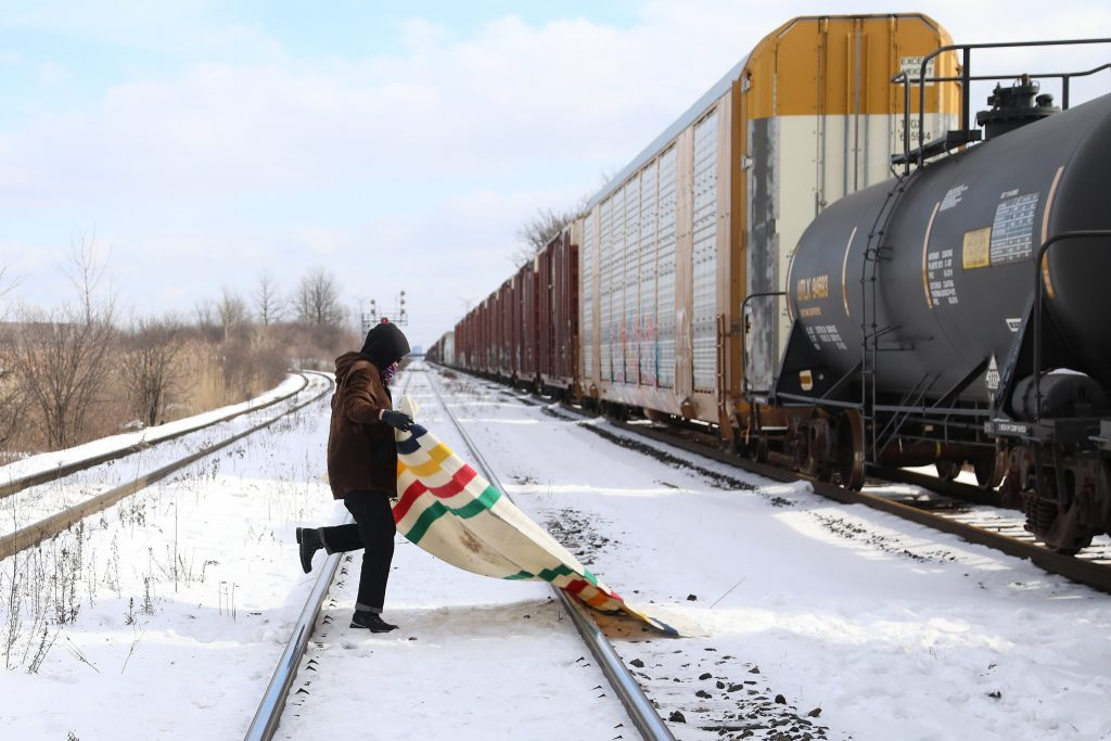 A protestor lays out a blanket on the tracks. Shut Down Canada protesters occupy the Macmillan Yard in Vaughan, Ontario in solidarity with Wet'suwet'en land defenders. All trains going west to Hamilton, London, New York and Michigan are now blocked as of 10 a.m. on Saturday. Emergency Action to stop RCMP invasion of Wet'suwet'en territory.